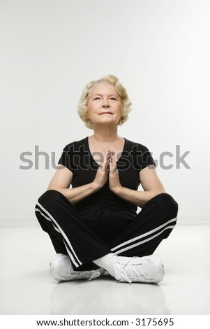 Caucasian senior woman sitting in yoga position on floor meditating. - stock photo