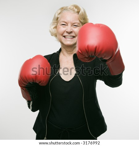 Caucasian senior woman wearing boxing gloves and throwing punch at viewer. - stock photo