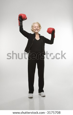 Caucasian senior woman wearing boxing gloves raised in the air.