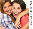 Caucasian sisters friends embracing and  laughing at camera - stock photo