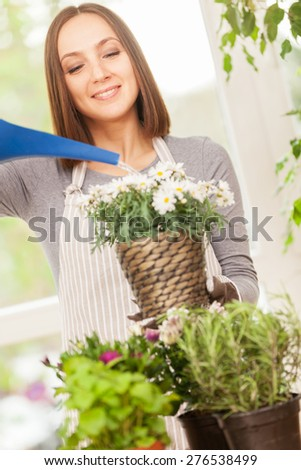 Caucasian smiling woman is pouring water in the plants - stock photo