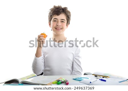 Caucasian smooth-skinned boy holding a tangerine with right hand while doing homework - stock photo