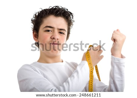 Caucasian smooth-skinned boy in white long sleeved t-shirt is puzzled while measuring the muscle of his left arms with yellow meter tape - stock photo