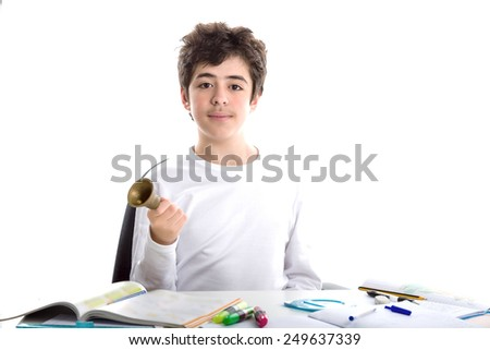 Caucasian smooth-skinned boy sitting ringing a small bell with right hand while doing homework - stock photo