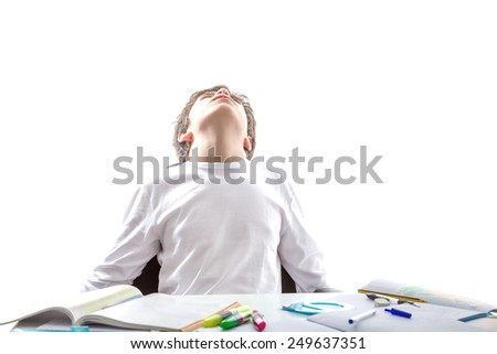 Caucasian smooth-skinned boy sitting while doing homework open arms looking at the sky with his head back - stock photo