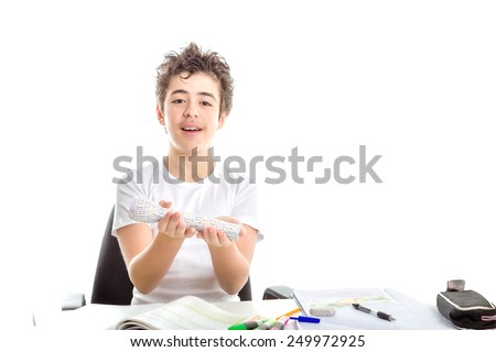 Caucasian smooth-skinned boy smiles holding 3D print labelled flashlight with both hands while doing  homework - stock photo