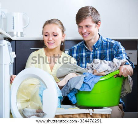Caucasian spouses doing regular laundry and smiling at home - stock photo