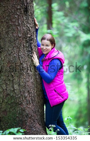 Caucasian standing woman in evergreen forest
