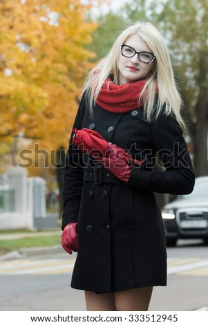 Caucasian student girl with red fully collapsible umbrella in hands and cat eye glasses is posing on autumn street with moving car and zebra crossing - stock photo