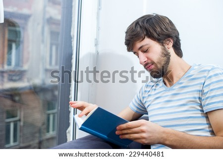 Caucasian student man reading a book while sitting on a blue sofa.