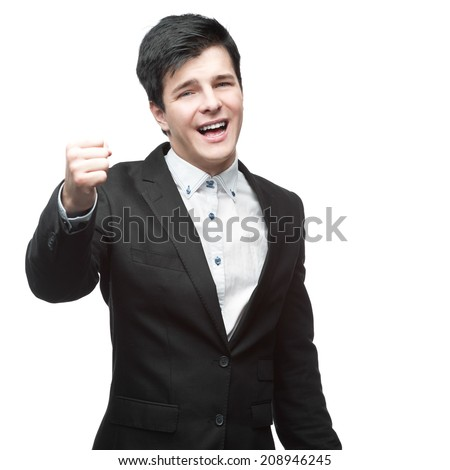 caucasian successful young businessman in black suit raised fist up isolated on white - stock photo