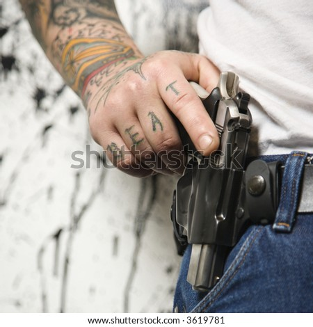 Caucasian tattooed man wearing holster with gun. - stock photo