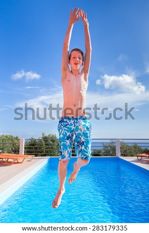 Caucasian teenage boy jumping high above blue swimming pool - stock photo