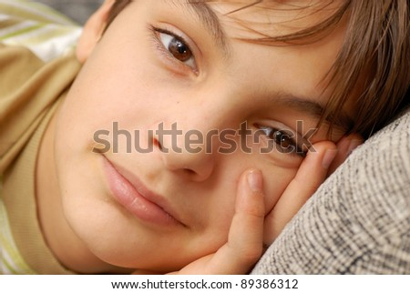 caucasian teenage boy portrait, resting with arm under cheek