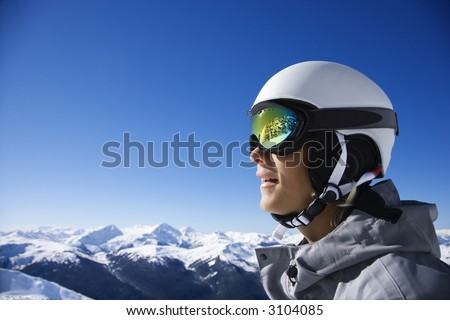 Caucasian teenage boy snowboarder wearing helmet and goggles on mountain in Whistler, British Columbia, Canada. - stock photo