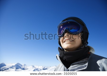 Caucasian teenage boy snowboarder wearing helmet and goggles on mountain in Whistler, British Columbia, Canada.