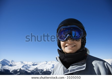 Caucasian teenage boy snowboarder wearing helmet and goggles on mountain looking at viewer Whistler, British Columbia, Canada. - stock photo