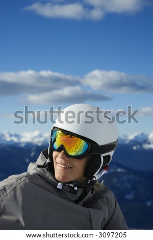 Caucasian teenage boy  snowboarder wearing helmet and goggles on mountain Whistler, British Columbia, Canada. - stock photo
