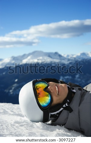 Caucasian teenage boy snowboarder wearing helmet and goggles, smiling, looking at viewer, lying in snow on mountain with mountain landscape in background Whistler, British Columbia, Canada. - stock photo