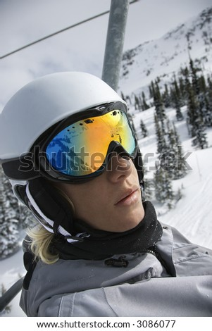 Caucasian teenage boy wearing helmet and goggles riding chair lift at ski resort in Whistler, British Columbia, Canada. - stock photo