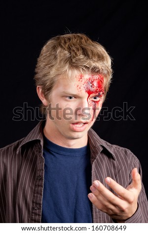 Caucasian teenage boy with blonde hair shocked look after serious head injury