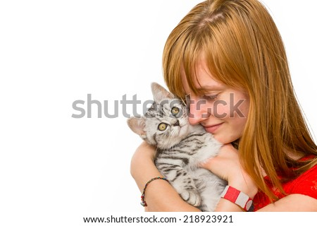 Caucasian teenage girl hugging young british short hair black silver tabby spotted cat isolated on white background - stock photo