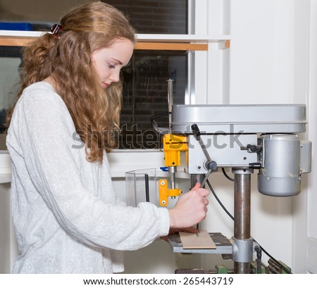 Caucasian teenage girl operating electric drilling machine. The european girl with long hair drills a hole in a piece of wood during technique lesson on high school. learning practice in education - stock photo