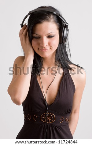 Caucasian teenage girl with happy smiling facial expression using headphones. - stock photo