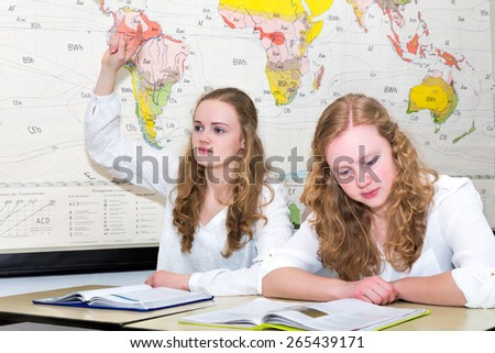 Caucasian teenage girl with learn finger in geography lesson. Two european sisters sitting side by side in high school class. One is reading a textbook to prepare for her study. - stock photo