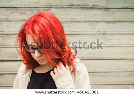 Caucasian teenager girl in glasses with bright red hair, closeup outdoor portrait over green grungy wooden wall - stock photo