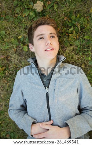 Caucasian teenager laying down on grass looking up - stock photo