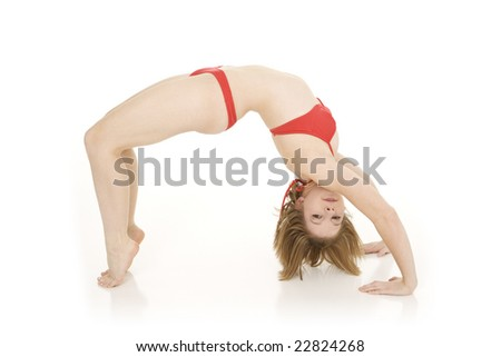 Caucasian teenager practicing yoga in a red bikini on a white background - stock photo