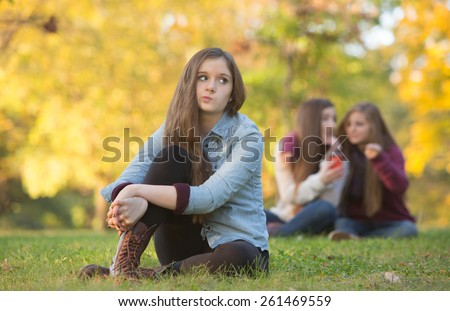 Caucasian teenager wondering about girls talking behind her - stock photo