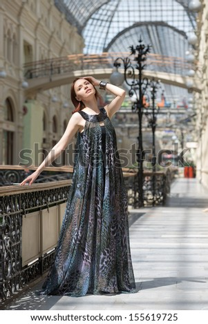 Caucasian tender young model is posing in a short black dress and lengthy transparent cape at old fashioned building with pillars