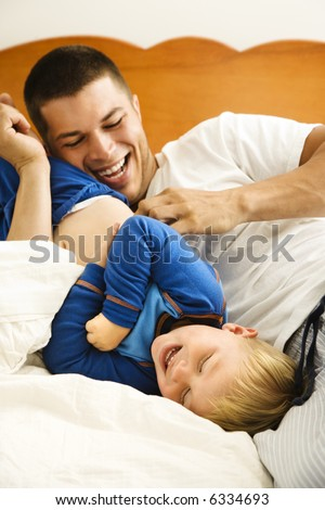 Caucasian toddler boy and father playing and tickling in bed. - stock photo