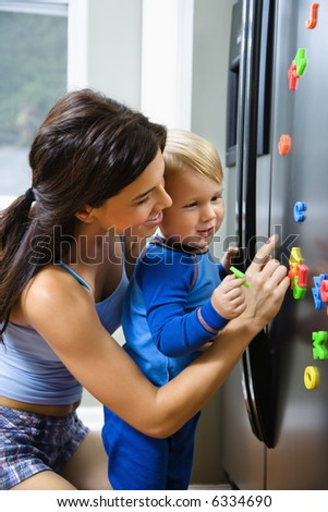 Caucasian toddler boy and mother playing with magnets on refrigerator. - stock photo