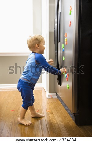 Caucasian toddler boy playing with magnets on refrigerator. - stock photo