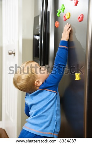 Caucasian toddler boy reaching for magnets on refrigerator. - stock photo
