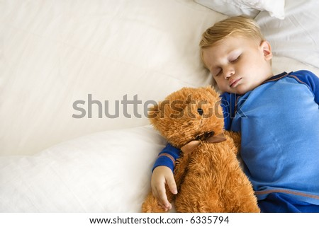 Caucasian toddler boy sleeping in bed with teddy bear. - stock photo
