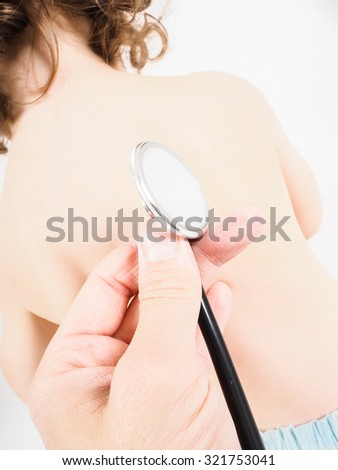 Caucasian toddler with back towards pediatrician with stethoscope towards bright background