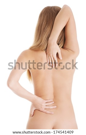 Caucasian topless woman touches her back. Isolated on white.