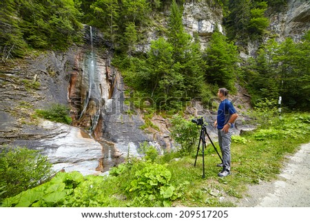 Caucasian tourist taking photos of a waterfall in the mountains - stock photo