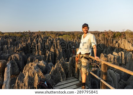 Caucasian tourist with camera at the panorama viewpoint at the Tsingy de Bemaraha Strict Nature Reserve in Madagascar - stock photo