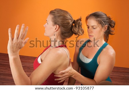 Caucasian trainer checks the shoulder of an athlete