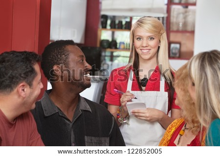 Caucasian waitress taking orders from diverse group of customers - stock photo