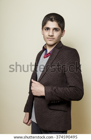 Caucasian white boy wearing black brown isolated inside off white background in studio - stock photo