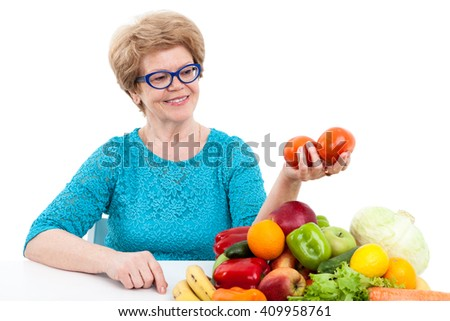 Caucasian woman a pensioner looking at tomatoes in hand while sitting near fresh fruit and vegetables, isolated on white background - stock photo