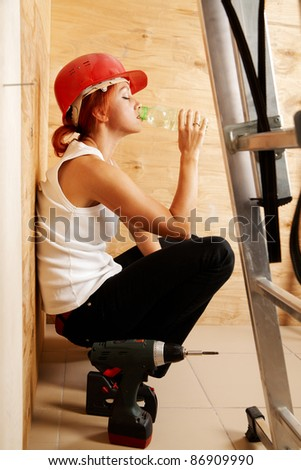 caucasian woman as worker wearing red protective helmet - stock photo