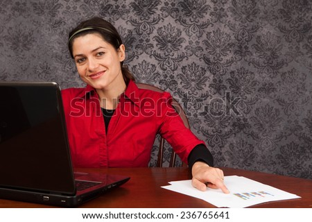 Caucasian woman at home on a laptop computer working with a set of reports - stock photo
