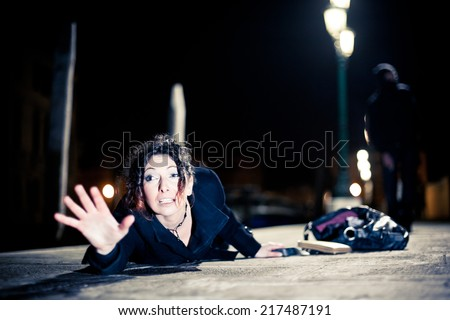 Caucasian woman being assaulted by a man in a dark alley.  Aggression concept. - stock photo